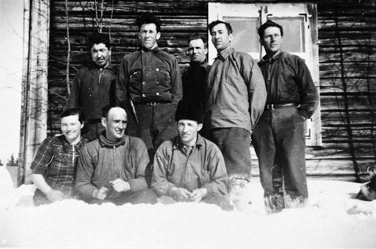 Timmerarbetare poserar i snön.